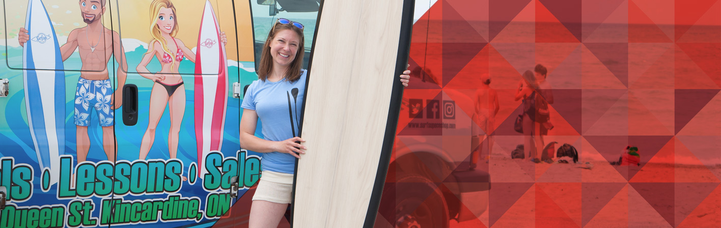 woman standing with surfboard in front of a truck