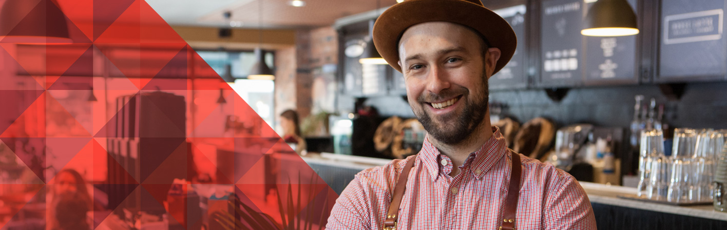 Smiling bearded man wearing a fedora and apron standing in a coffee shop