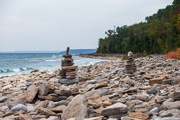 Two innuksuks stand among the rocks on the shore of the lake.