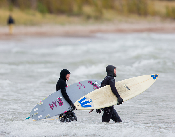 Two surfers with boards walk into the water.