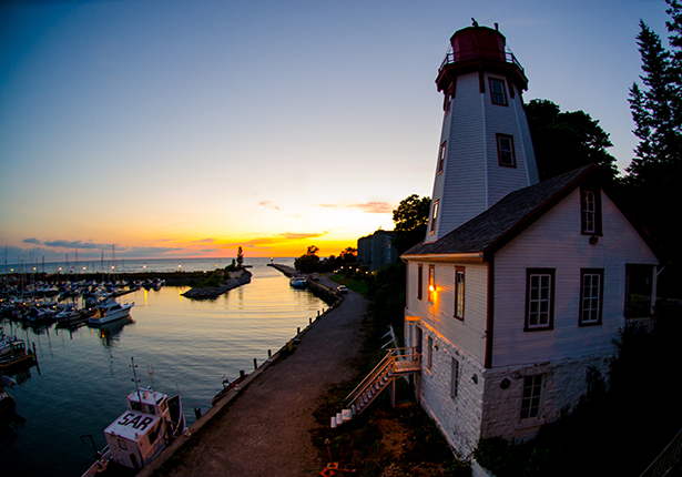 A lighthouse is semi-silhouetted by the sunset over the water.