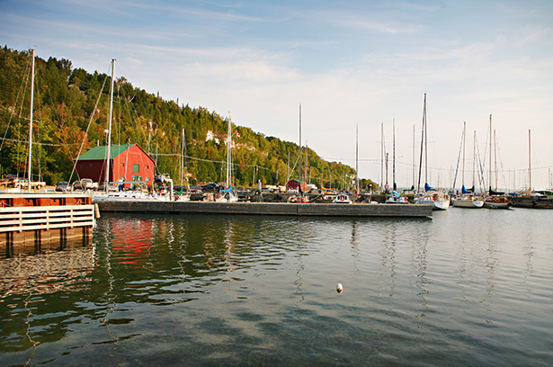 A dock and red boathouse are surrounded by moored sailboats.