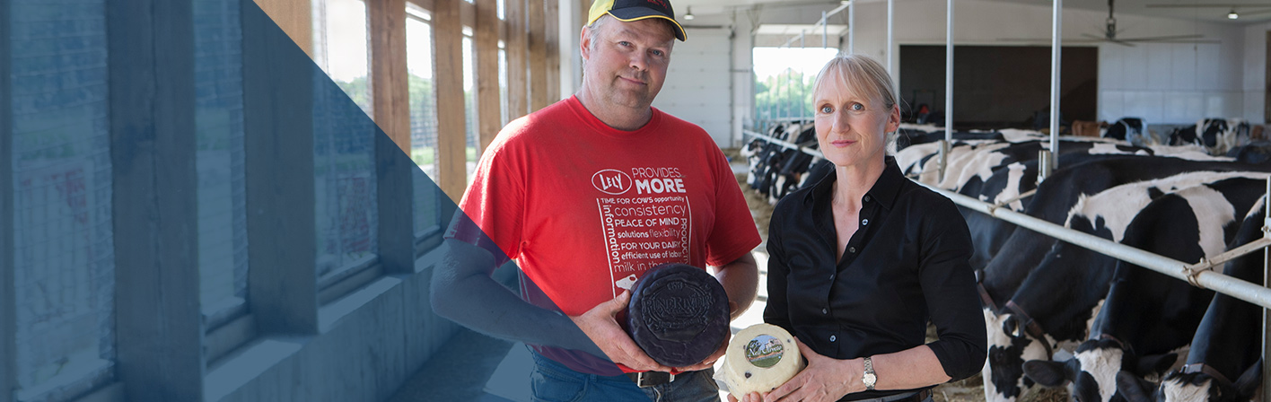 A man and a woman standing in a diary barn holding wheels of cheese